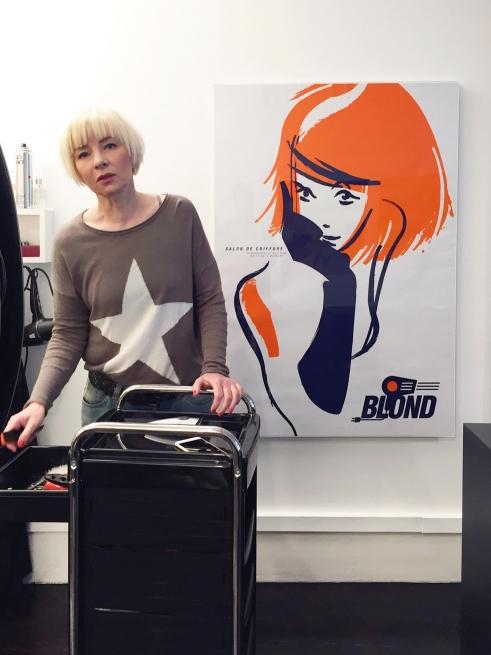 Monic in front of Blond Salon de Coiffure poster